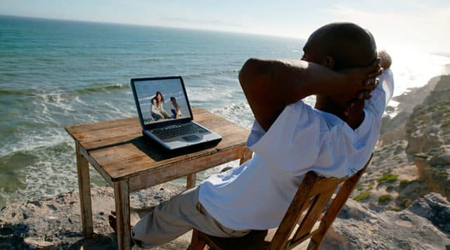 Man relaxing with his laptop near the beach