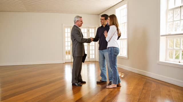 Couple shaking hands with a real estate agent