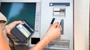 Person inserting a credit card into an ATM machine