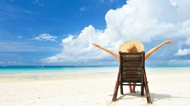 Woman sitting on a lounge chair and enjoying the beach view