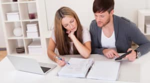Young couple calculating income and expenses