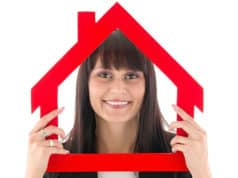 Woman holding up an outline of a house