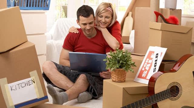 Couple unpacking cardboard boxes