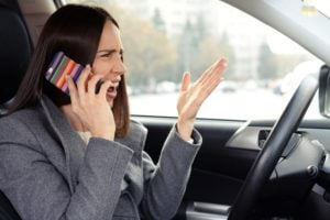 Woman angrily talking on the phone in a car